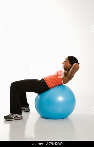 Side view of African American woman balancing on exercise ball doing crunches - Stock Photo
