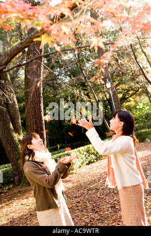 Two young women catching falling leaves - Stock Photo