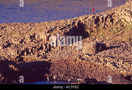 Person on the hexagonal columns of Giants Causeway Co Antrim Northern Ireland - Stock Photo