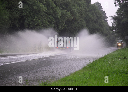 Car driving through flooded road spraying water after heavy rain - Stock Photo