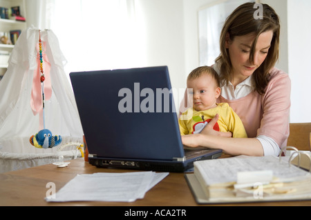 Young mother with baby, working on her laptop - Stock Photo