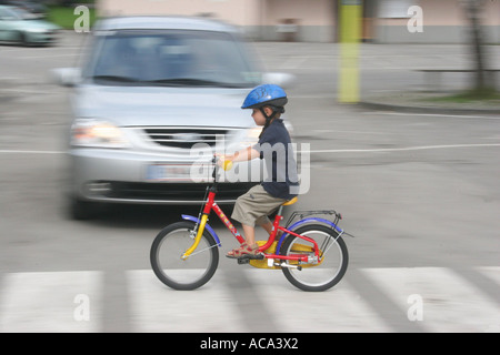 Child with a bicycle on pedestrian crossing - Stock Photo