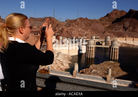Hoover Dam water inlet towers Colorado River border between Nevada and Arizona states USA, tourist taking a photograph - Stock Photo