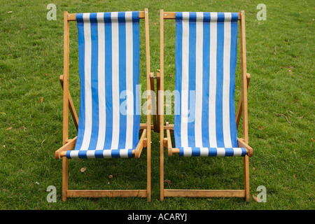 two blue and white stripped empty deckchairs in a park london england uk - Stock Photo