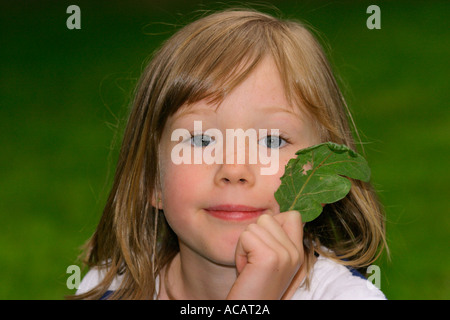 Portrait of young six year old girl with leaf - Stock Photo
