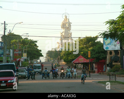 Street scene at oversized Maddona statue at sunset, Voncepcion, Paraguay - Stock Photo