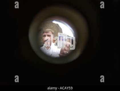 Police officer demonstrates a spy hole in a front door UK - Stock Photo