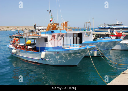 fishing boats moored in the clear water of Cefalu harbour on the north coast of Sicily - Stock Photo
