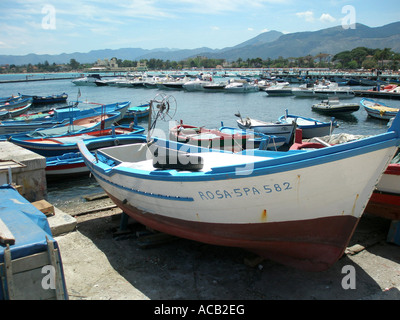 Fishing boats pulled ashore in Cefalu harbour, on the North coast of Sicily - Stock Photo