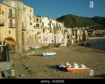 Boats and a pedalo on the he sandy beach which fronts the small town of Cefalu on the North coast of Sicily - Stock Photo