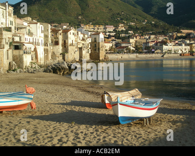 Boats on the he sandy beach which fronts the small town of Cefalu on the North coast of Sicily - Stock Photo