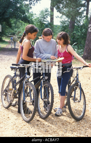 Three teenage girls in countryside with bikes looking at map for route directions - Stock Photo