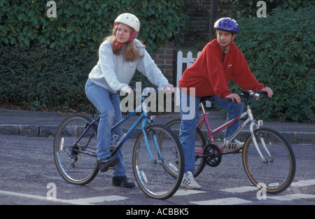 Two teenagers wearing safety helmets out on bikes waiting at give way road sign - Stock Photo