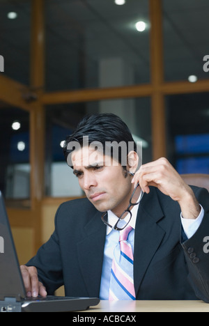 Businessman using a laptop in an office and thinking - Stock Photo