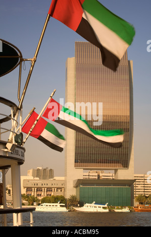 The National Bank of Dubai Building with Emirates national flags flying from the stern of a boat in the foreground. - Stock Photo