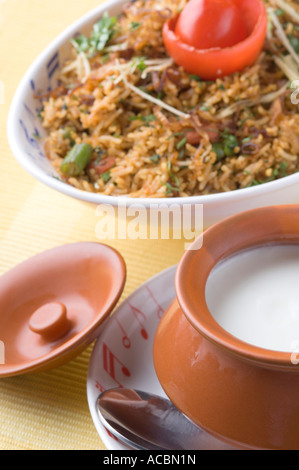 Close-up of a bowl of fried rice with a bowl of curd on a plate - Stock Photo