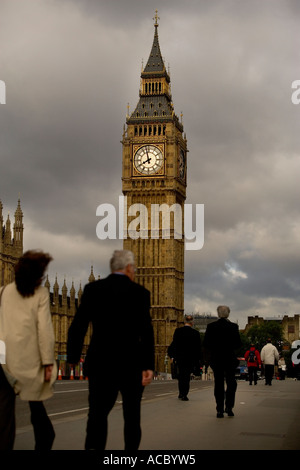 Businessmen and women pedestrians crossing the Westminster Bridge under the Big Ben clock tower near parliament - Stock Photo