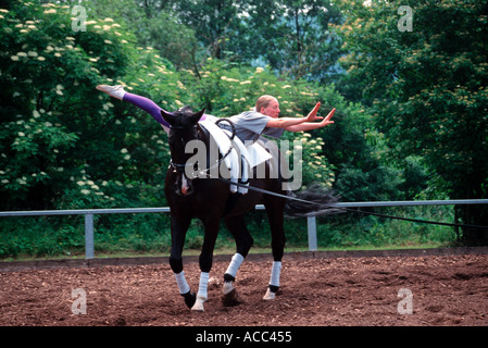 young girl training and warming up before starting at a voltige tournament in Bavaria Germany - Stock Photo