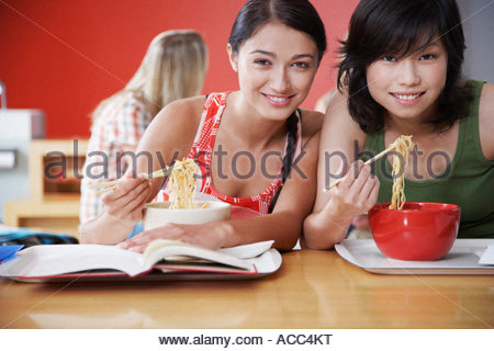 Teenage girls eating bowl of noodles with chopsticks in cafeteria - Stock Photo