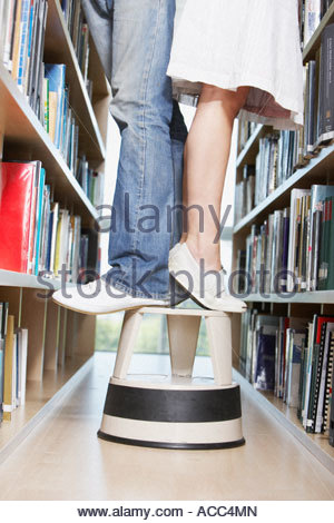 Waist down girl and boy standing on step stool in library - Stock Photo