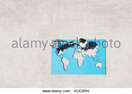 Two people standing on world map outdoors holding hands - Stock Photo