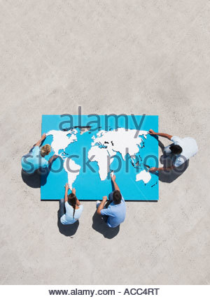 Aerial View of four people doing world map puzzle - Stock Photo