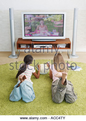Two young girls watching television eating popcorn - Stock Photo