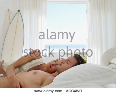 A couple in bed sleeping - Stock Photo