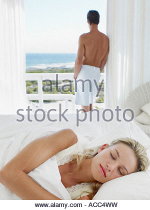Woman sleeping in bed while a man looks out the window - Stock Photo
