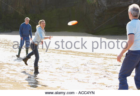 Three adults playing Frisbee on the beach - Stock Photo