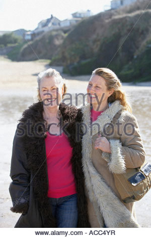 one mature and one senior woman on the beach - Stock Photo