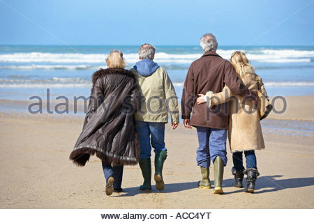 two couples strolling on the beach - Stock Photo