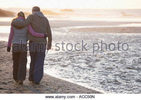 couple happily embracing walking down the beach - Stock Photo