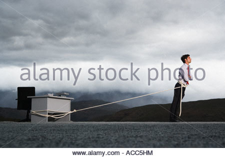 Man attempting to pull his desk outdoors with a long rope - Stock Photo