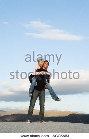 Man giving woman a piggy-back ride - Stock Photo