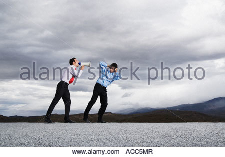 Businessman with megaphone outdoors shouting at man - Stock Photo