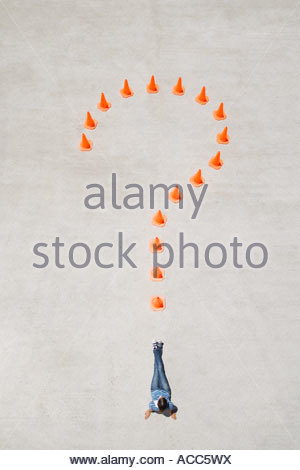 Traffic cones forming question mark with woman at point lying down - Stock Photo