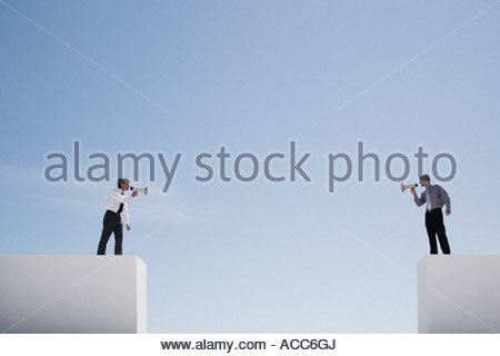 Businessmen with megaphones on walls with gap shouting - Stock Photo