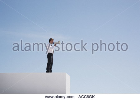 Businessman with megaphone on wall shouting - Stock Photo
