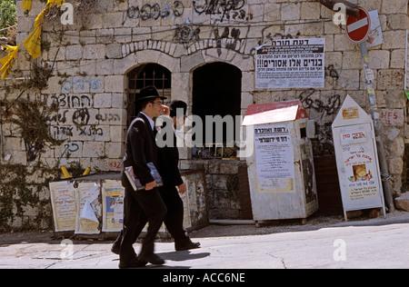 Jewish men walking up street in Mea Sharim, Jerusalem - Stock Photo