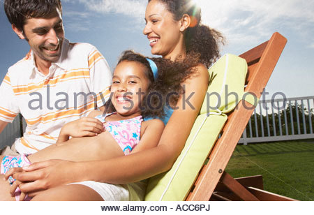 Woman and man with girl snuggling outdoors in summer - Stock Photo