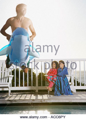 Man on flotation device leaping into pool with girls laughing - Stock Photo