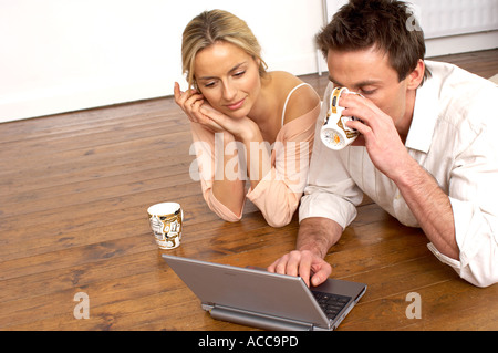 couple laying on wooden floorboards using a laptop computer - Stock Photo