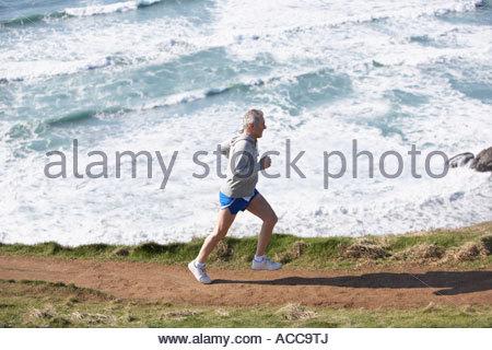 man running on the beach - Stock Photo