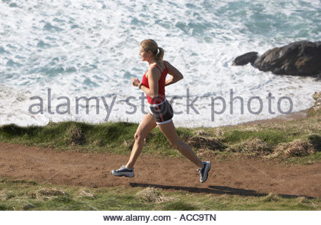 Woman running on the beach - Stock Photo