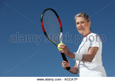 senior woman serving a tennis ball - Stock Photo