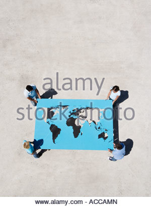 Four people holding world map outdoors - Stock Photo