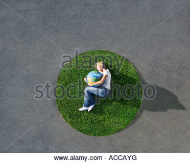 Woman lying down on circle of grass on pavement with globe - Stock Photo