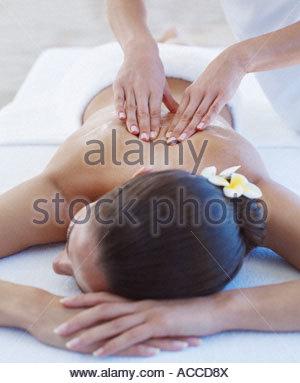 Masseuse giving a woman a back massage - Stock Photo