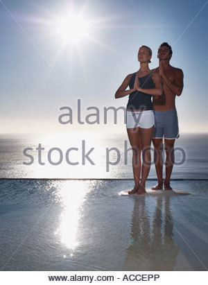 A man and woman doing yoga by tranquil waters - Stock Photo